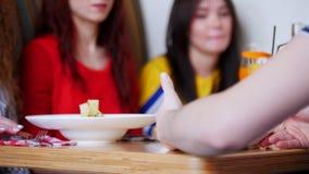Freundinnen, die in einem Café sitzen Tabelle voll der verschiedenen Nahrung und der Getränke Eine Person gegenüber von ihnen nim stock video footage