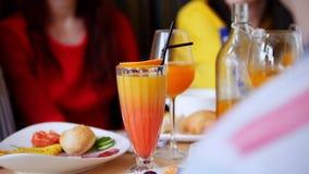 Freundinnen, die in einem Café sitzen Tabelle voll des Lebensmittels und der Getränke stock video footage