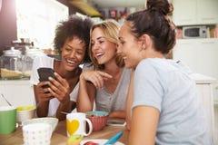 Freundinnen, die Frühstück essen, während, Handy überprüfend lizenzfreie stockbilder