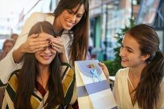 Freundinnen, die Geburtstagsgeschenk geben Mädchen überraschte ihren Freund stockbilder