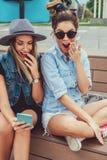 Freundinnen, die Handy entsetzt betrachten stockfotos