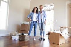 Freundinnen, die im Aufenthaltsraum des neuen Hauses an beweglichem Tag stehen stockfotos