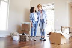 Freundinnen, die im Aufenthaltsraum des neuen Hauses an beweglichem Tag stehen lizenzfreie stockfotografie