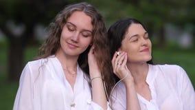 Freundinnen, die Musik hören stock footage
