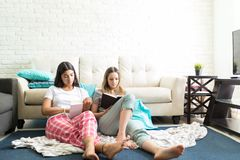 Freundinnen, die Roman beim Sitzen auf Boden lesen lizenzfreie stockfotografie