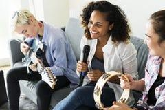 Freundinnen, die Spaß mit Musik zusammen spielen haben lizenzfreie stockbilder