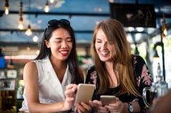 Freundinnen, die Telefon im Restaurant verwenden stockfoto