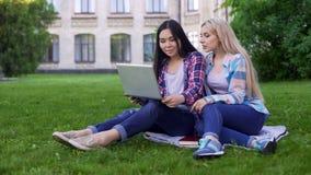 Freundinnen, die Video auf Laptop aufpassen und letzte Studentenpartei besprechen lizenzfreies stockfoto