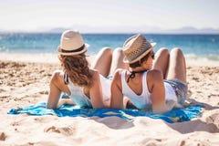 Freundinnen, die zusammen im Strand genießen stockbild