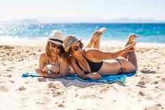Freundinnen, die zusammen im Strand genießen stockbilder