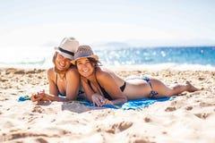 Freundinnen, die zusammen im Strand genießen stockfotos