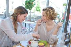 Freundinnen, die zusammen am Restaurant zu Mittag essen Stockfotografie