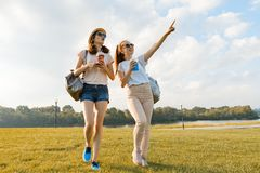 Freundinnen gehen in den Park in der Natur Mädchen gehen entlang den grünen Rasen, sprechen, haben Spaß stockfotografie