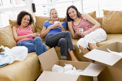Freundinnen mit Kaffee durch Kästen im neuen Haus Lizenzfreies Stockfoto