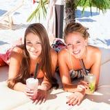 Freundinnen in trinkenden Cocktails der Strandbar lizenzfreies stockbild
