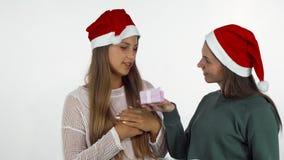 Freundinnen, welche die Weihnachtsgeschenke, neues Jahr feiernd austauschen stock footage