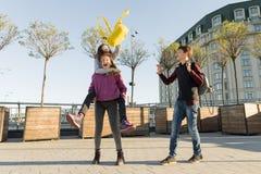 Freundjugendlichstudenten mit Schulrucksäcken, Spaß auf dem Weg von der Schule habend stockfotografie