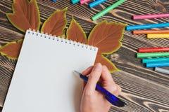 Freundlich weibliche Handschrift im leeren Notizbuch auf Holztisch Stockfoto
