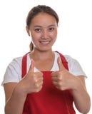 Freundliche chinesische Kellnerin, die sich beide Daumen zeigt lizenzfreies stockbild