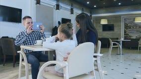 Freundliche europäische Familie, die Foto im Café während ihres Abendessens macht stock video