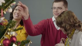 Freundliche Familie, die froh Weihnachtsbaum auf Vorabend des hellen Feiertags verziert stock video footage