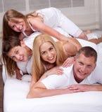 Freundliche Familie, die Spaß auf, hat einem Bett zusammen zu liegen Lizenzfreie Stockfotografie