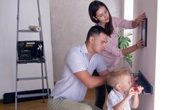Freundliche Familie mit dem kleinen Kinderjungen, der zu ummauern neu streichendes und schraubendes Regal und Bild tut stock video footage