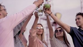 Freundliche Firma auf den Dachspitzenerhöhungsgläsern mit Cocktails herauf und Geklirr städtisches Cocktail des Sommers stock video footage