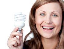 Freundliche Frau, die eine Glühlampe anhält Stockbild