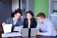 Freundliche Freunde von Studenten zwei Kerle und Mädchen sitzen an Co stockfotografie