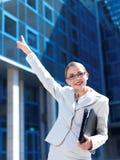 Freundliche Geschäftsfrau, die auf das Büro zeigt Stockbilder