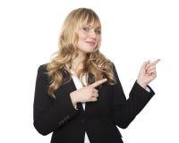 Freundliche Geschäftsfrau, die mit beiden Händen zeigt Stockbilder