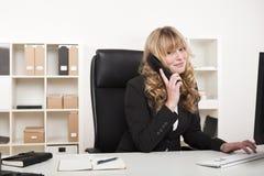 Freundliche Geschäftsfrau, die am Telefon plaudert Stockbilder