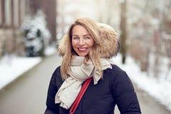 Freundliche junge blonde Frau draußen im Winter Stockfoto