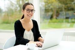 Freundliche junge Frau, die draußen an einem Laptop arbeitet stockbild