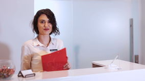 Freundliche junge Frau hinter dem Aufnahmeschreibtischverwalter stock footage