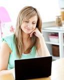 Freundliche kaukasische Frau, die zu Hause ihren Laptop verwendet Stockbild