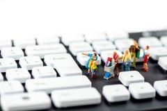 Freundliche Miniaturfamilie, die Computertastaturen betrachtet Getrennt auf Weiß Lizenzfreies Stockbild