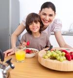 Freundliche Mutter und ihr Kind, die frühstückt Lizenzfreie Stockfotos