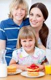 Freundliche Mutter und ihre Kinder, die Waffeln essen stockfoto
