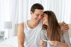 Freundliche Paare mit einer Schwangerschaftprüfung Stockfoto
