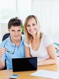 Freundliche Paare unter Verwendung eines Laptops, der zusammen sitzt lizenzfreie stockfotos