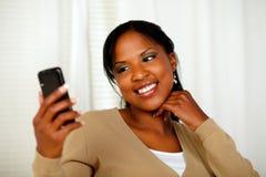 Freundliche schwarze Frau, die eine Textmeldung sendet Lizenzfreie Stockfotos