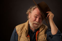 Freundlicher älterer Mann, der seinen Hut spitzt Stockbilder