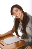 Freundlicher aufgeregter asiatischer Student durch Schreibtisch lizenzfreie stockfotos