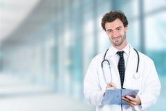 Freundlicher Doktor mit der lächelnden Stellung des Klemmbrettes in der Krankenhaushalle Lizenzfreie Stockfotos