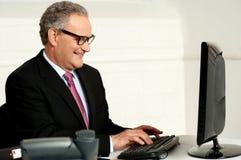 Freundlicher gealterter Mann, der an Computer arbeitet Lizenzfreie Stockfotografie