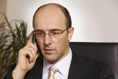 Freundlicher Geschäftsmann auf Handy Lizenzfreie Stockfotografie