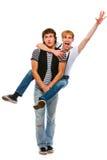 Freundlicher Jugendlicher, der seinen Freund huckepack trägt Stockfotos