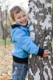 Freundlicher Junge, der Birken, Herbstpark umarmt Stockfotografie